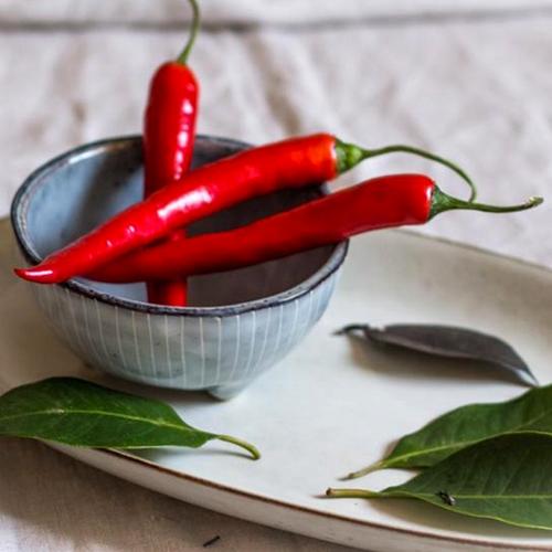 Afbeelding van drie rode pepers in een schaaltje