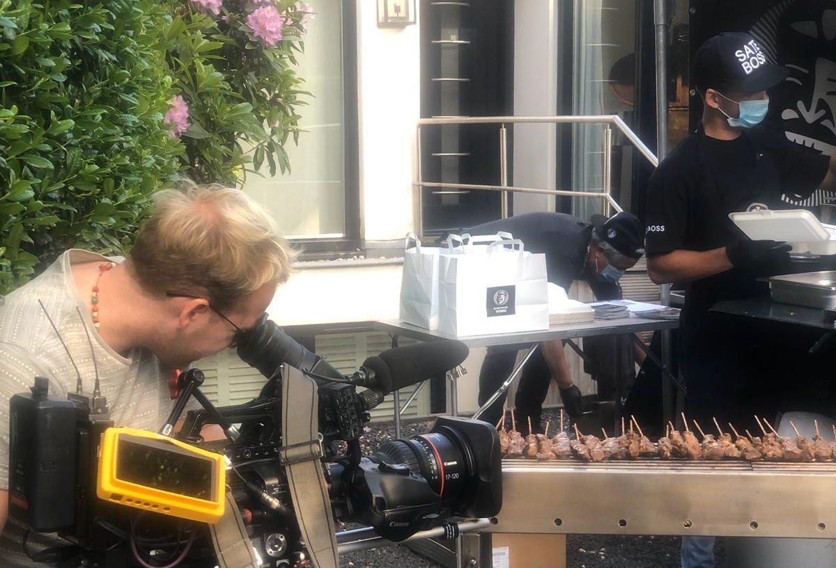 Cameraman van EenVandaag (AVROTROS) filmt Satesboss op locatie bij deelname aan Buurtkeukens